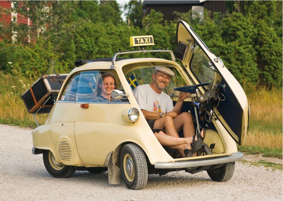 Ein Paar in einer cremefarbenen Isetta mit Taxi-Schild auf dem Dach.