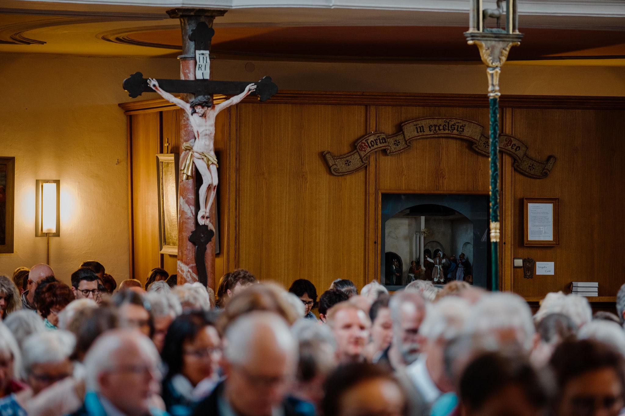 Ein Blick über die Köpfe der Gottesdienstbesucher*innen auf ein Kruzifix.