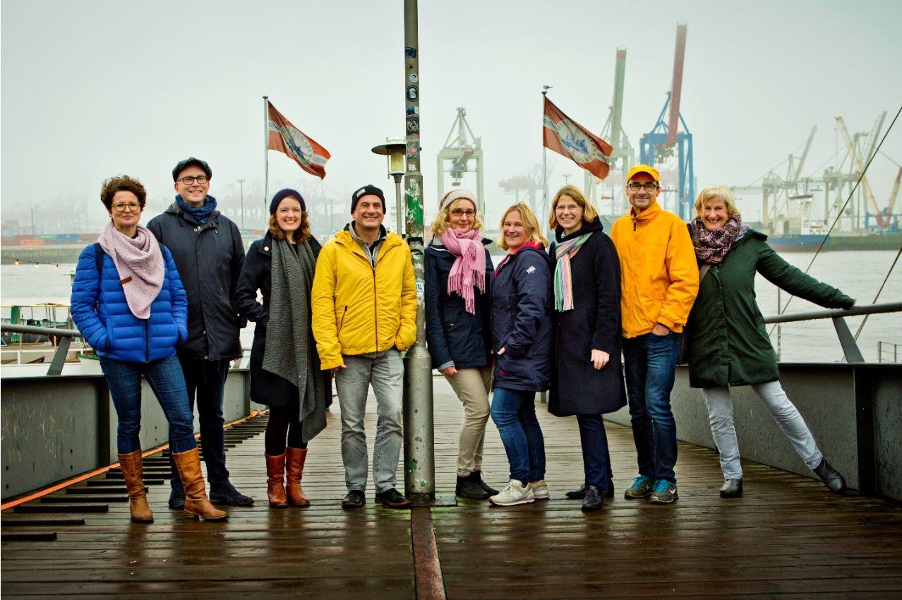 Die redaktion des Anderen Advent an einem grauen Wintertag auf dem Anleger zum Museumshafen Neumühlen an der Elbe.