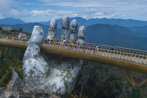 Das Titelbild des Flyers für den Missionspreis 2021 zeigt ein Motiv aus Da Nang in Vietnam: Eine überdimensionierte steinerne Hand, über die Menschen auf einer Brücke gehen, die Golden Bridge.