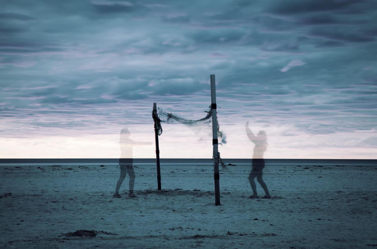 Schemen von zwei Frauen, die am Strand bei wolkigem Himmel Volleyball spielen.