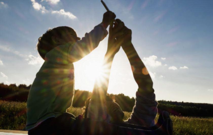 Eine Junge und sein Vater machen ein Selfie im Sonnenlicht